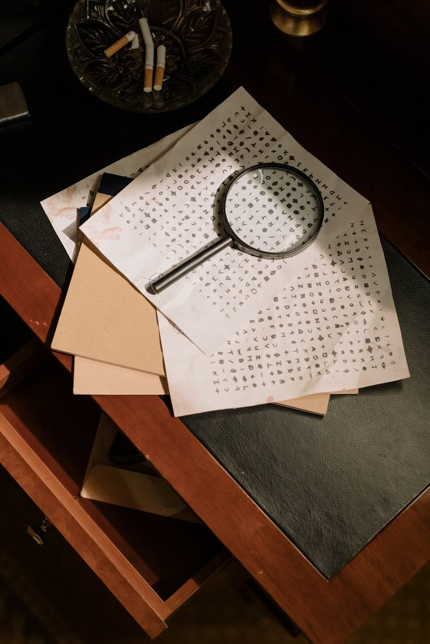 Sheets of paper sit on a writing desk with a magnifying glass on top. Decorative.